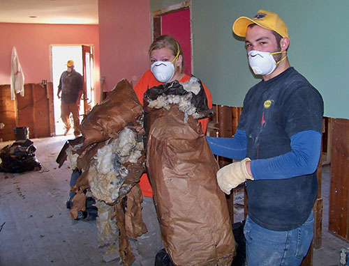 Sophmore social work major Mollie Jones and Sophmore chemistry major Nic McGuire remove moldy insulation from house affected by Hurricane Sandy.